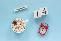 Zima skład Biali drewniani kalendarzowi sześciany Dane Luty 14th Filiżanka kakao z marshmallow i czerwień budzikiem obraz royalty free