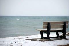 Zima, spadek/ Fotografia ławka na oceanu koszcie z trochę śnieg na ziemi Błękitne wody ocean jest na plecy zdjęcia stock