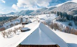 Zima w Rumunia chłopa tradycyjnych domach zakrywających w śniegu w Sirnea wiosce blisko otręby i Brasov, Transylvania, Rumunia zdjęcia stock