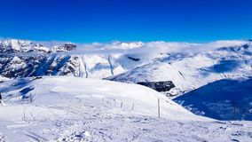Zima wakacje w Alps górach pod niebieskim niebem Zdjęcia Royalty Free