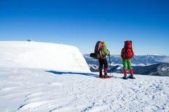 Zima wycieczkuje w górach na karplach z namiotem i plecakiem Zdjęcie Stock