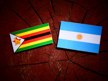 Zimbabwe flag with Argentinian flag on a tree stump isolated Royalty Free Stock Image