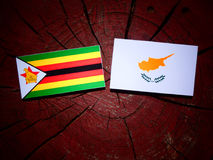 Zimbabwe flag with Cypriot flag on a tree stump isolated Stock Images
