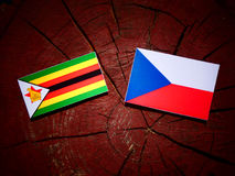 Zimbabwe flag with Czech flag on a tree stump  Royalty Free Stock Photography