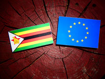 Zimbabwe flag with EU flag on a tree stump isolated. Zimbabwe flag with EU flag on a tree stump Royalty Free Stock Photography
