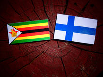 Zimbabwe flag with Finnish flag on a tree stump isolated Royalty Free Stock Images