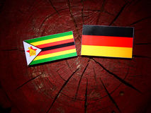 Zimbabwe flag with German flag on a tree stump  Stock Images