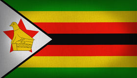 Zimbabwe flag. National flag of zimbabwe with orange, yellow, black and green stripes with a big white triangle at the left side and a bird over a stand and a Stock Photos