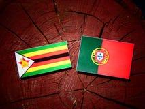 Zimbabwe flag with Portuguese flag on a tree stump isolated. Zimbabwe flag with Portuguese flag on a tree stump royalty free illustration