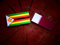Zimbabwe flag with Qatari flag on a tree stump isolated. Zimbabwe flag with Qatari flag on a tree stump Royalty Free Stock Image