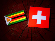 Zimbabwe flag with Swiss flag on a tree stump isolated Stock Images
