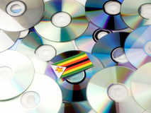 Zimbabwe flag on top of CD and DVD pile  on white Stock Photography