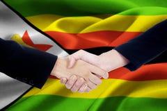 Zimbabwe flag with two entrepreneurs handshake Royalty Free Stock Photography