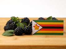 Zimbabwe flag on a wooden panel with blackberries isolated on a Stock Image