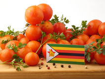 Zimbabwe flag on a wooden panel with tomatoes isolated on a whit Stock Photos