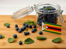 Zimbabwe flag on a wooden plank with blueberries  on whi Royalty Free Stock Photos