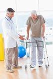 zimmer框架的老人与治疗师 免版税库存图片