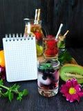 Zimna detox woda z organicznie owoc, jagodami i notatnik i Zdjęcie Royalty Free