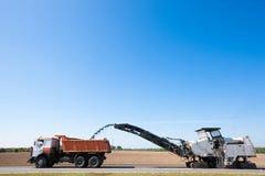 Zimna strugarka usuwa przetartego asfalt w dumper ciężarówkę zdjęcia stock