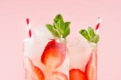 Zimni truskawkowi napoje z kawałkami owoc, kostka lodu, mennica, słoma na eleganckim różowym tle, zbliżenie, odgórna sekcja, kraw zdjęcia royalty free