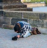 Zimny Bezdomny mężczyzna błaga dla pieniądze od turystów na Charles moście w Praga na jego kolanach - wiosna 2019 obrazy royalty free