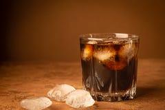 Zimny koktajlu napój z lodem w szkle na ciemnego brązu tle Zakończenie Selekcyjna ostrość kosmos kopii fotografia stock