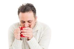 Zimny mężczyzna trzyma kubek gorąca herbata obraz stock