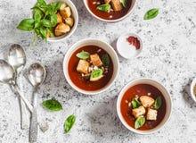 Zimny pomidorowy zupny gazpacho z croutons i basilem na lekkim tle Jarski jedzenie Zdjęcia Royalty Free