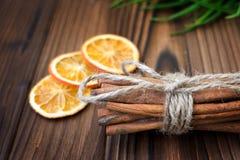 Zimt, getrocknete Orangen und Anis auf braunem Holztisch Lizenzfreies Stockfoto