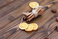 Zimt, getrocknete Orangen und Anis auf braunem Holztisch Lizenzfreie Stockfotos
