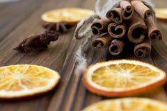 Zimt, getrocknete Orangen und Anis auf braunem Holztisch Stockfotos