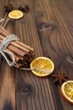 Zimt, getrocknete Orangen und Anis auf braunem Holztisch Stockbild