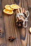 Zimt, getrocknete Orangen und Anis auf braunem Holztisch Lizenzfreie Stockbilder