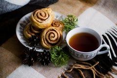 Zimtgebäckbrötchen mit Gewürzen und Tee Kanelbulle - schwedischer süßer selbst gemachter Nachtisch Weihnachtsbäckereigebäck stockfoto
