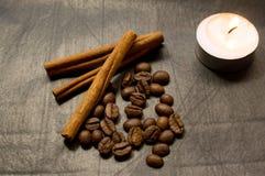 Zimtstangen, Kaffeebohnen, brennende Kerze Stockfoto
