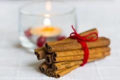 Zimtstangen mit roter Schnur und brennender Kerze Stockfoto