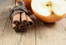 Zimtstangen und Apfel auf Holztischbestandteil lizenzfreie stockfotos