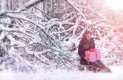 Zimy bajka, młoda dziewczyna w lasu A dziewczynie z prezentami w wigilię nowego roku w parku Fotografia Stock