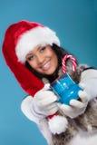 Zimy dziewczyny Santa pomagiera kapelusz trzyma błękitnego kubek Obraz Royalty Free