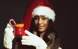 Zimy dziewczyny Santa pomagiera kapelusz trzyma czerwonego kubek Zdjęcia Royalty Free