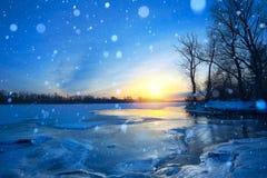Zimy krajobrazowa panorama; zmierzch na banku zamarznięta rzeka; Zdjęcia Royalty Free