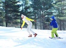 Zimy młoda uśmiechnięta matka bawić się z syna dzieckiem iść narciarstwo obraz stock