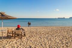 Zimy morza plażowy i spokojny morze na słonecznym dniu Osamotniona starsza kobieta siedzi w pokładu krześle stawia czoło morze Pa zdjęcia stock