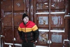 Zimy spojrzenie silny mężczyzna Samiec jest ubranym w czerwonej żółtej czarnej barwionej puszek kurtce przemysłowe tło Zdjęcie Royalty Free