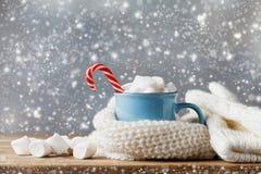 Zimy styl życia z filiżanką gorący kakao z marshmallows i trykotowym szalikiem na drewnianym tle Śnieżny skutek zdjęcia stock