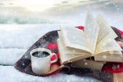 Zimy wciąż życie: filiżanka kawy i otwierająca książka zdjęcia royalty free