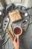 Zimy wygodny pojęcie Szarość dziali pulower, filiżankę herbata, giftbox i zegarki na popielatym tle, obrazy stock