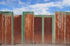 Zinc fence on blue sky Royalty Free Stock Photos