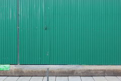Zinc fence green on pavements Royalty Free Stock Photography
