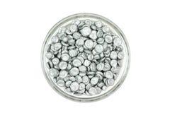 Zinc granules in a glass dish Stock Photo